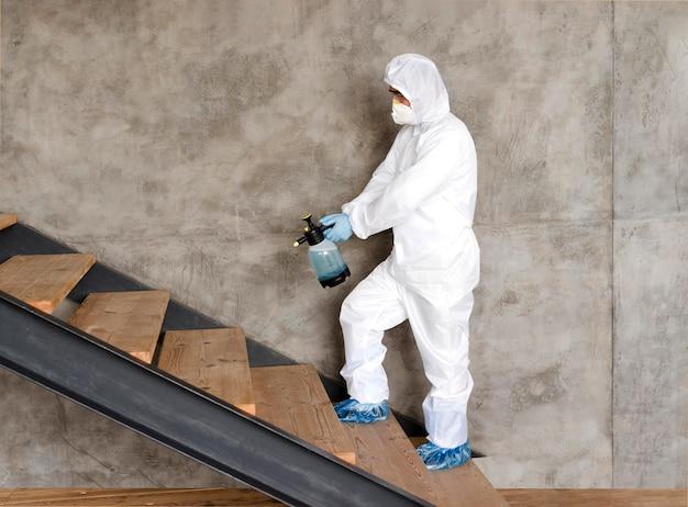 Tiro completo hombre desinfectando escaleras