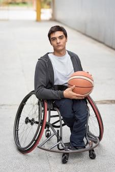 Tiro completo hombre discapacitado sosteniendo baloncesto
