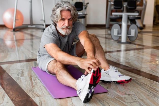 Tiro completo hombre estirando en el gimnasio