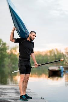 Tiro completo hombre posando con remo y canoa