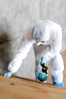 Tiro completo hombre con traje desinfectando escaleras