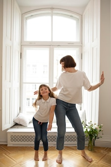 Tiro completo madre y niña bailando