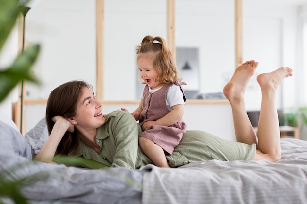 Tiro completo madre y niña en la cama