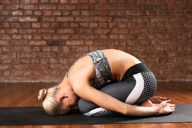 Tiro completo mujer agachada en estera de yoga