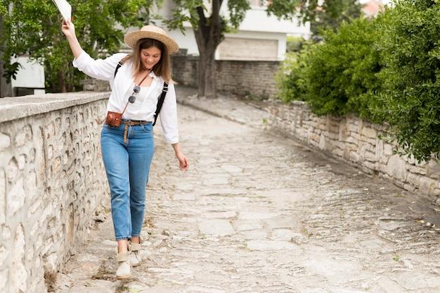 Tiro completo mujer caminando en el callejón