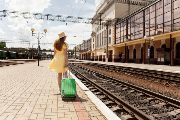 Tiro completo mujer en la estación de tren