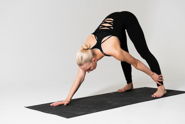 Tiro completo mujer haciendo ejercicio en estera