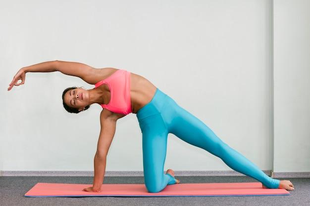 Tiro completo mujer haciendo ejercicio con los ojos cerrados