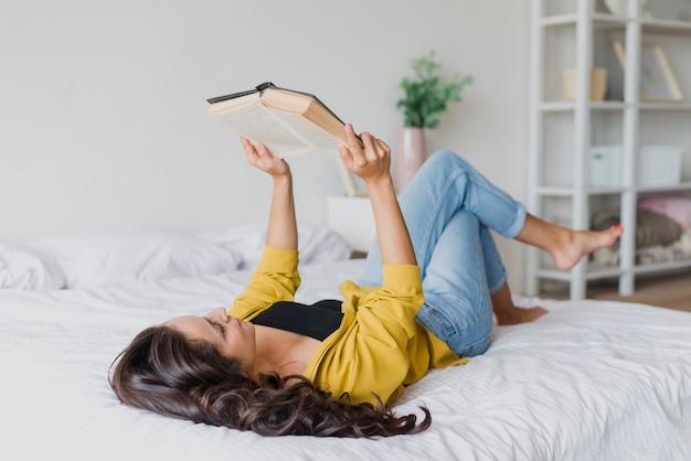 Tiro completo mujer leyendo en la cama