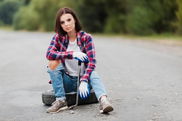 Tiro completo de mujer con una llave inglesa sentado en el neumático