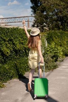 Tiro completo mujer llevando equipaje verde