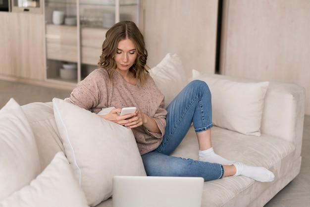 Tiro completo mujer mirando smartphone