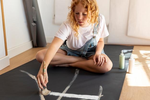 Tiro completo mujer en la pintura del piso