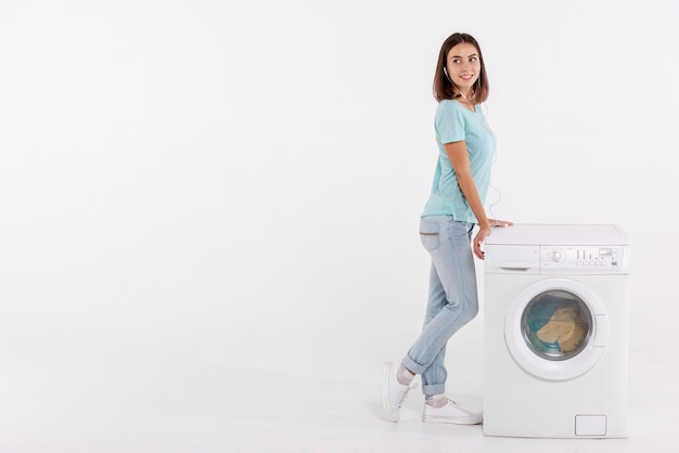 Tiro completo mujer posando junto a la lavadora