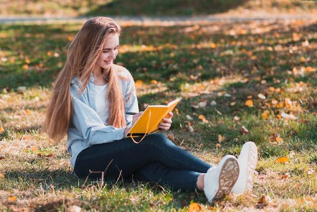 Tiro completo mujer rubia escribiendo en un cuaderno