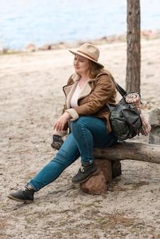 Tiro completo mujer sentada al aire libre