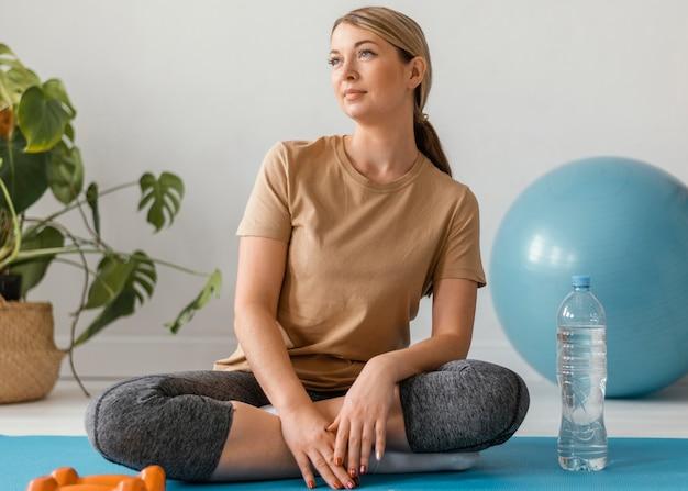 Tiro completo mujer sentada en estera de yoga