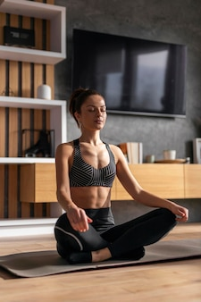 Tiro completo mujer sentada en la estera de yoga
