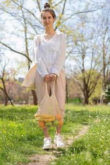 Tiro completo mujer sosteniendo una bolsa reutilizable con comida en la naturaleza