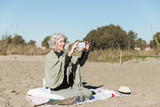Tiro completo mujer tomando fotos en la playa