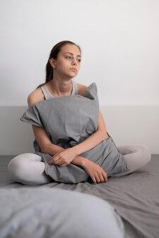 Tiro completo mujer triste sosteniendo la almohada