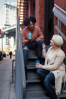 Tiro completo mujeres sentadas en las escaleras