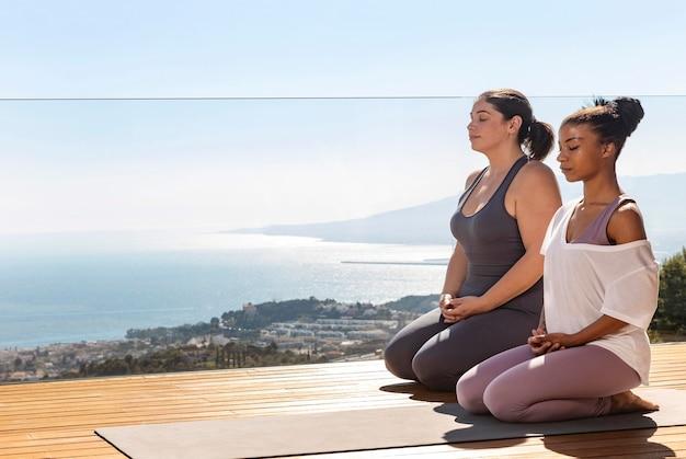 Tiro completo mujeres sentadas en estera de yoga