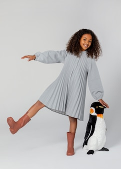 Tiro completo niña feliz posando con pingüino
