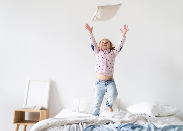 Tiro completo niña jugando con una almohada