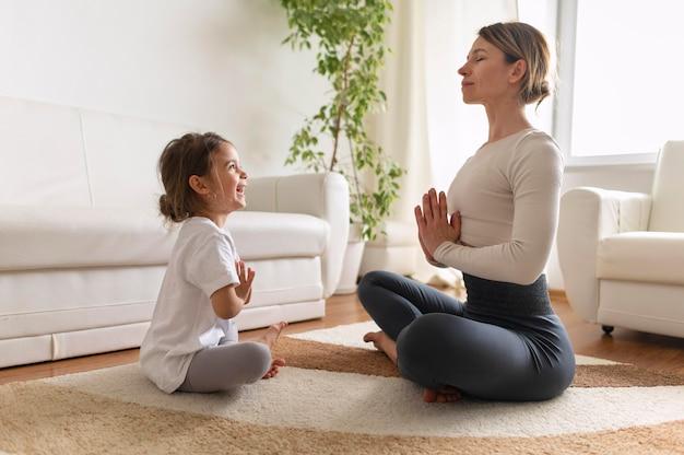 Tiro completo niña y mujer meditando