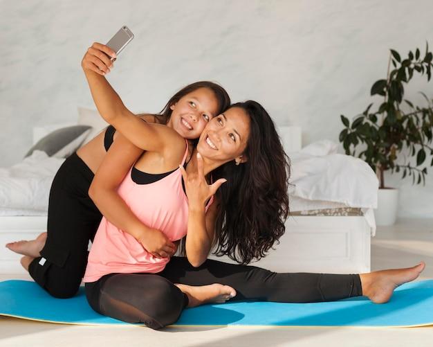 Tiro completo niña y mujer tomando selfie