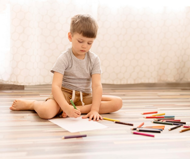 Tiro completo niño dibujando en el piso