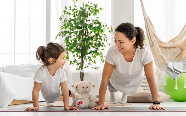 Tiro completo niño y mujer haciendo plancha