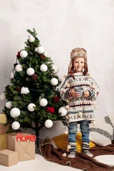Tiro completo niño sonriente cerca del árbol de navidad