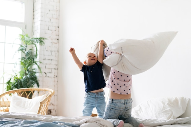 Tiro completo niños peleando con almohadas