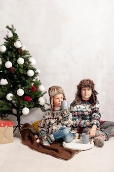 Tiro completo niños sentados cerca del árbol de navidad