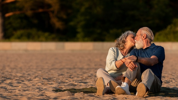 Tiro completo, pareja mayor, besar, en, playa