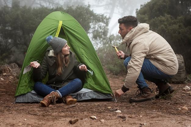Tiro completo de personas en el bosque con carpa