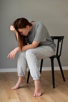 Tiro completo triste mujer sentada en una silla