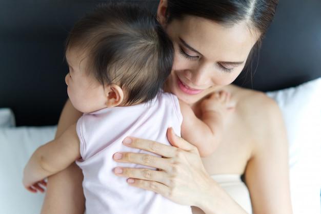 Tiro de la cosecha de la madre asiática hermosa que celebra la parte posterior del bebé en la cama.