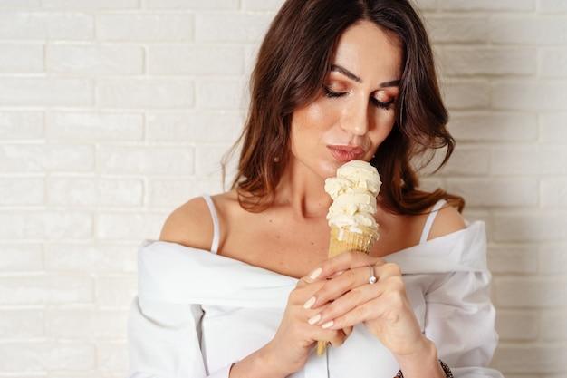 Tiro de la cosecha de la mujer joven atractiva con helado