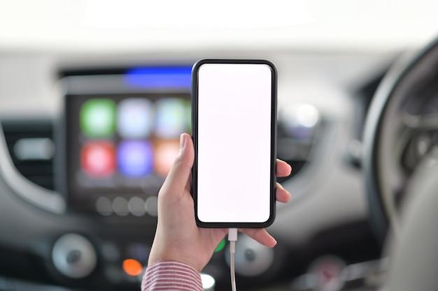 Tiro cosechado de la mano femenina que sostiene el teléfono móvil en coche.