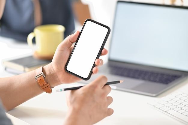 Tiro cosechado de la mano del hombre de negocios que sostiene el teléfono móvil de la pantalla en blanco en la oficina