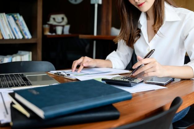 Tiro cosechado de la pluma de tenencia de la mujer joven y usar la calculadora mientras que se sienta en el escritorio de oficina