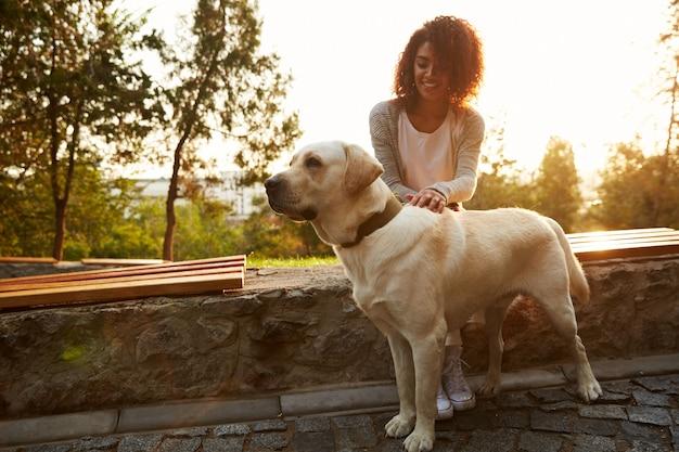 Tiro de cuerpo entero de perro blanco bonito con dueño en park walking