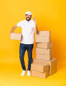 Tiro de cuerpo entero del repartidor entre cajas sobre amarillo aislado con los dedos cruzados y deseando lo mejor