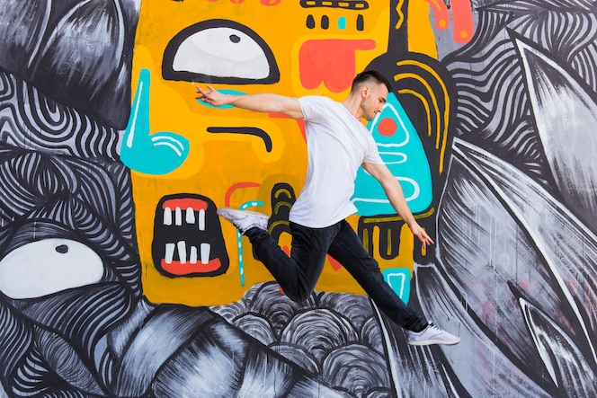 Tiro de mediados del aire de hombre guapo contra la pared de graffiti