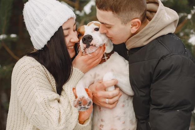 Tiro de estilo de vida de pareja en bosque nevado con perro