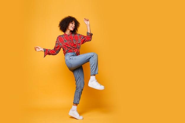 Tiro del estudio de la muchacha negra que salta con la expresión feliz de la cara en fondo anaranjado brillante. usa jeans, zapatillas blancas y camisa roja.