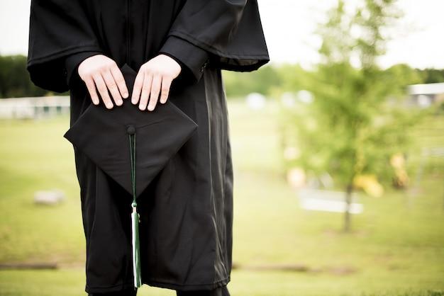 Tiro de foco superficial de un graduado sosteniendo su sombrero